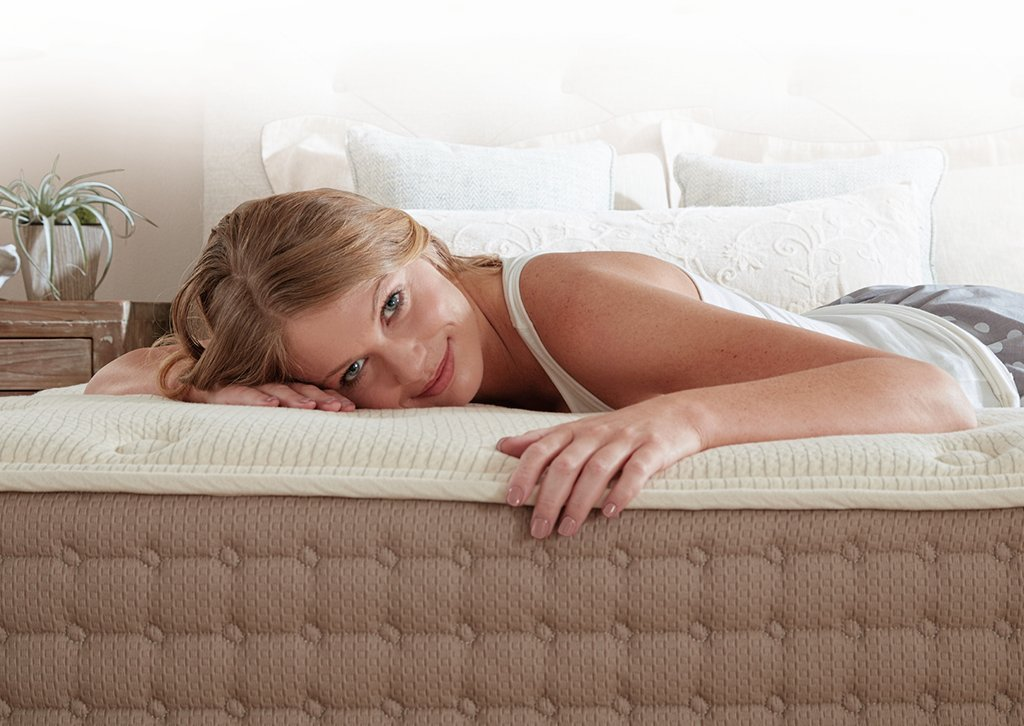 A woman lies on the Eco Terra mattress which features a 3-inch layer of Talalay latex foam and a fabric encased spring coil system.