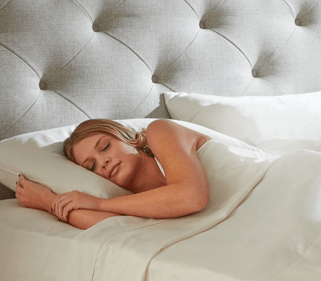An attractive woman getting rejuvinating sleep on the Plush Beds Luxury Bliss mattress without being exposed to any of the toxic chemicals or fire retardants that are typically found in polyurethane mattresses.
