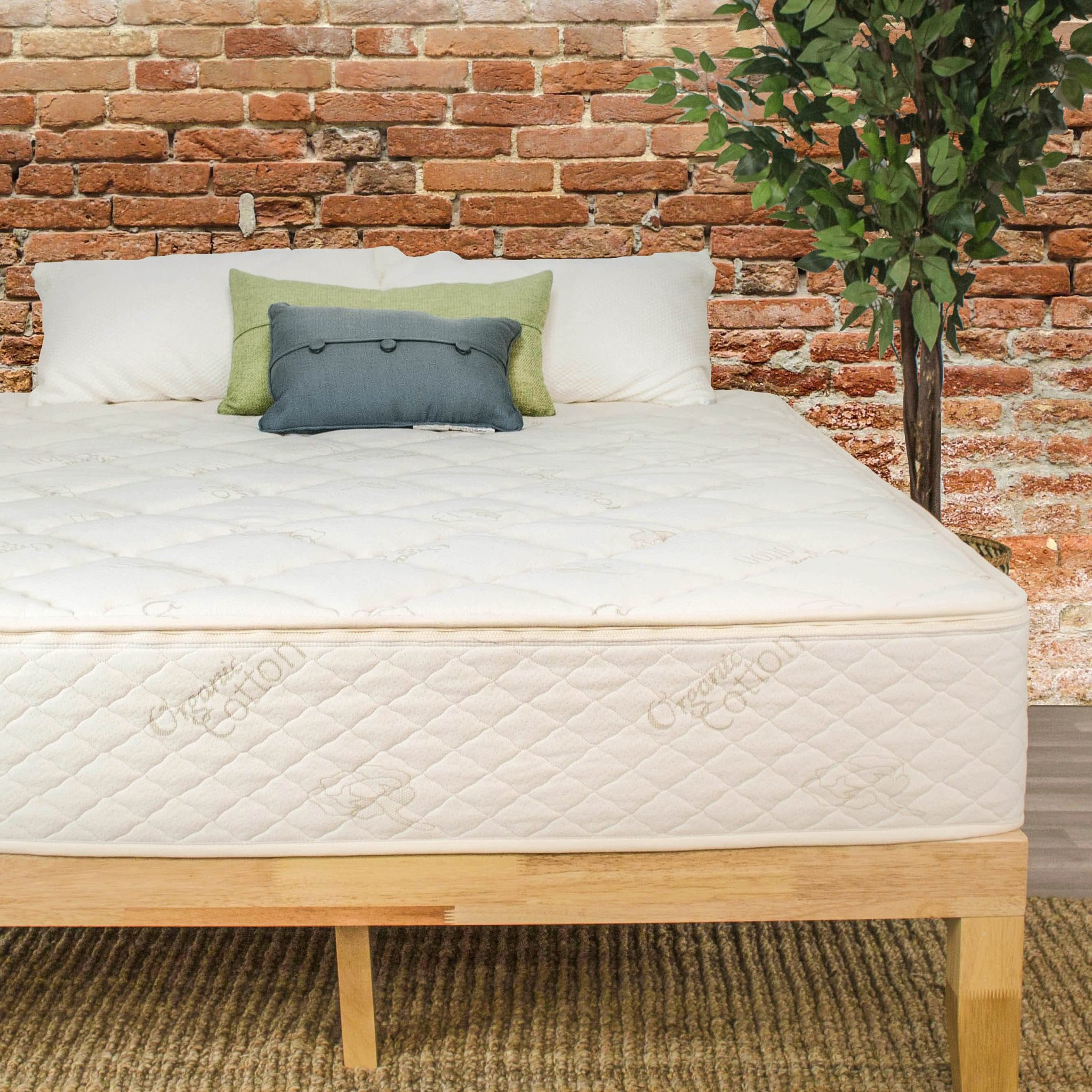 The Natural Latex Mattress by Sleep EZ set up on a wooden bed frame in a room that has a brick wall